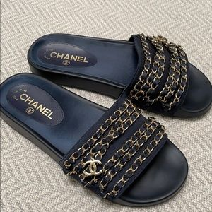 CHANEL navy slides gold chain and CC charms.